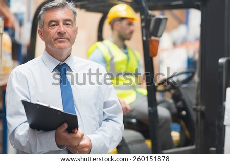 Manager posing in front of his employee in warehouse - stock photo
