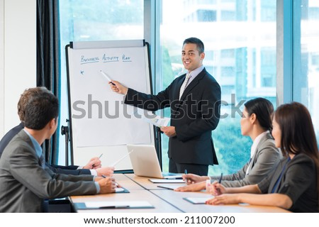 Manager presenting business activity plan to his colleagues - stock photo
