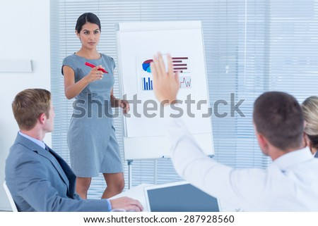 Manager presenting statistics to her colleagues in the office - stock photo