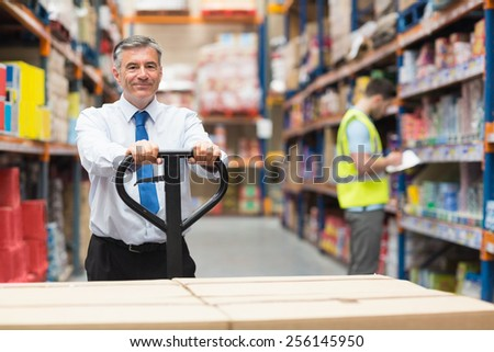 Manager pulling trolley with boxes in front of his employee in warehouse - stock photo