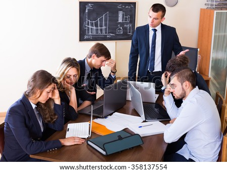 Manager shouting to employees at group meeting indoors - stock photo