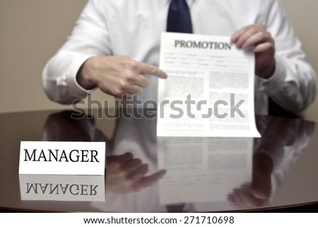 Manager sitting at desk holding Promotion document for employee