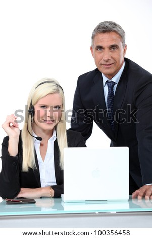 Manager talking to an employee in a headset - stock photo