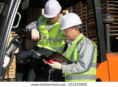 manager talking to forklift driver in a warehouse - stock photo
