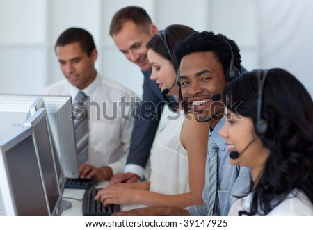 Manager talking to his multi-ethnic business team in a call center