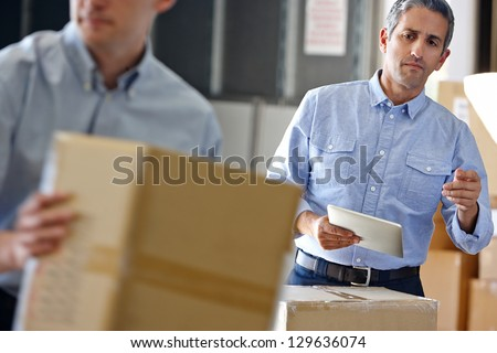 Manager Using Tablet Computer In Distribution Warehouse - stock photo