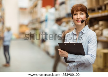 Manager wearing a headset while holding clipboard in a large warehouse - stock photo