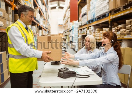 Manager wearing yellow vest giving box to his colleague in a large warehouse - stock photo