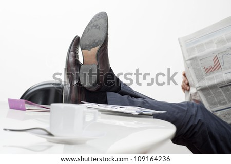 manager with feet on desk and cup of coffee