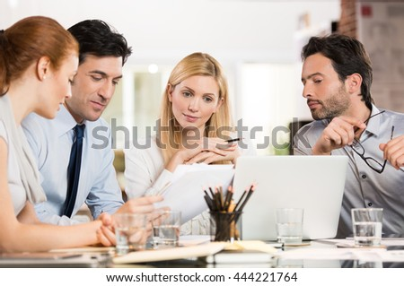 Manager with his colleague discuss about the business plan. Business team working at office. Business meeting in a conference room analyzing corporate reports. - stock photo