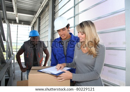 Manager with store-men controlling goods delivery - stock photo
