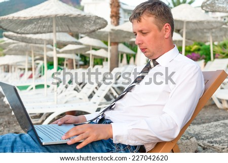 Manager working on a laptop on the beach