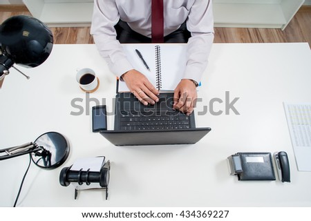 manager works in office behind the desk / man in office