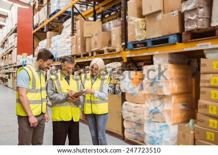Manager writing on clipboard talking to colleague in a large warehouse - stock photo