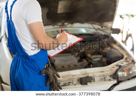 Manager writing with pencil on clipboard cost repair  - stock photo
