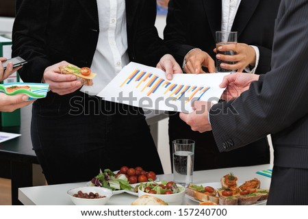 Managers analyzing chart at a business lunch - stock photo