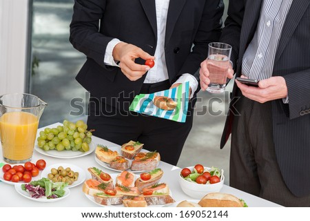 Managers at office buffet during business lunch - stock photo