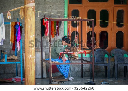 MANALI, HIMACHAL PRADESH, INDIA - 5 SEP: Woman weaves a colorful shawl on a traditional spinning machine on the veranda of the house in the Kullu Valley, Himachal Pradesh, India on 5 SEP 2015. - stock photo