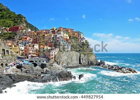 MANAROLA, ITALY - JUNE 17 2016: Manarola is the oldest town in the Cinque Terre and local people have built colorful houses on rocky, steep territory overlook the Liguria sea.