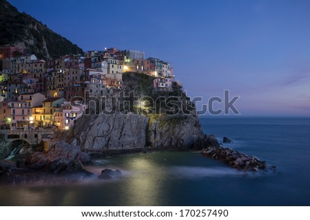 Manarola village on cliff rocks and sea at sunset., Seascape in Five lands, Cinque Terre National Park, Liguria Italy Europe. Square format. Long Exposure - stock photo