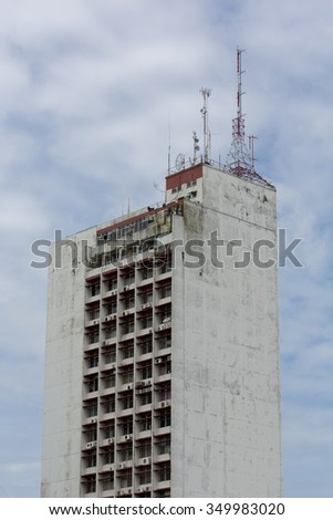 MANAUS, BRAZIL, MARCH 21: Vintage modern and dirty tall residential building with telecommunication antennas on the roof in Manaus, Amazonas State. Brazil 2015 - stock photo