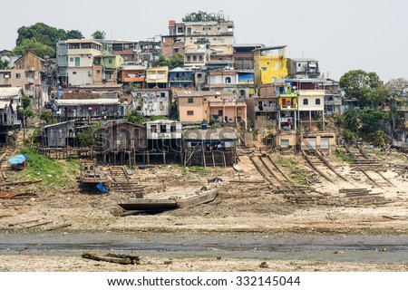 MANAUS, BRAZIL - OCTOBER 18, 2015: Concrete and shanty wooden plank homes climb up hillside above heavily littered stream emptying into Rio Negro in Manaus, Amazonas, Brazil - stock photo