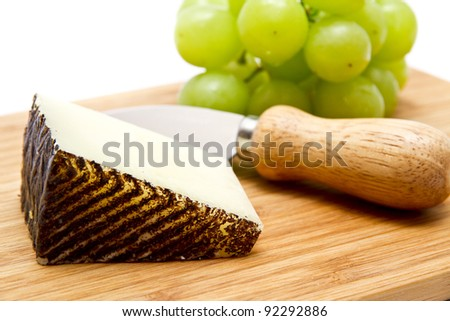 Manchego cheese and green grapes on chopping board - stock photo