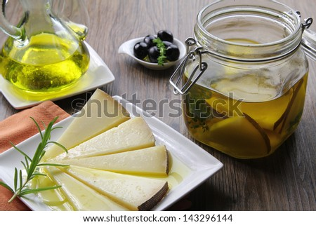manchego cheese in extra virgin olive oil tapas - stock photo