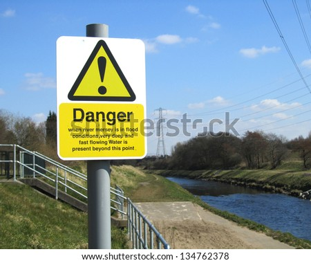 MANCHESTER, ENGLAND, APRIL 6: Warning sign next to the River Mersey in Didsbury, Manchester, England on April 6 2013. The sign is next to a sluice gate which is used to control water levels and prevent floods.