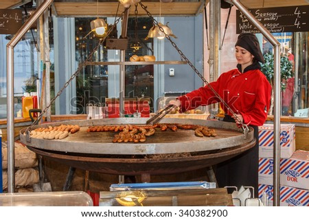 Manchester,England - November 16th: German sausages cooking on a huge swinging grill at the Manchester 2015 Christmas market.  The sausages are being cooked by a  girl in red traditional costume. - stock photo