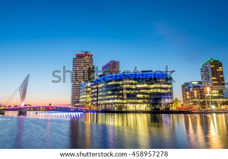 MANCHESTER - MAY 22: Foot bridge cross Manchester ship canal, connecting between Media City and Imperial War Museum at Salford quays in Manchester city, England, under twilight sky, on May 22, 2016.