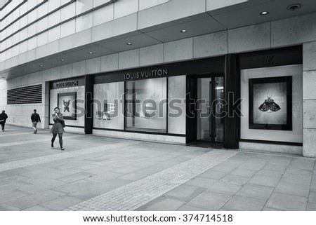 MANCHESTER, UK - APRIL 22, 2013: Shoppers walk past Louis Vuitton in Manchester, UK. Forbes says that LV was the most powerful luxury brand in the world in 2008 with $19.4bn USD value. - stock photo
