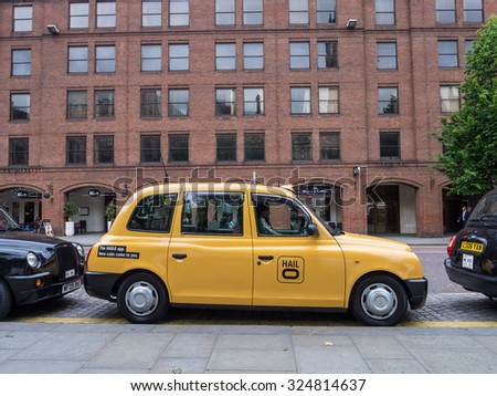 MANCHESTER, UNITED KINGDOM - JUNE 18, 2015: Typical yellow taxi in Manchester, United Kingdom.