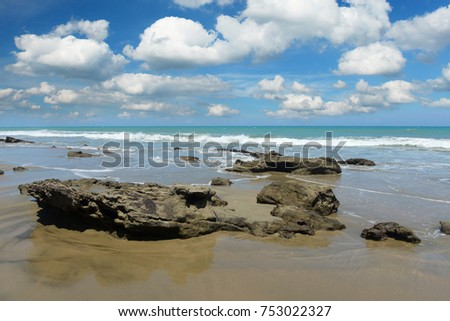 Mancora Beach with rocks in the foreground and clouds