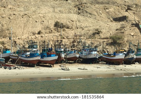 MANCORA, PERU - AUGUST 17, 2013: Old wooden fishing boats and some rafts on sandy beach on August 17, 2013 in Mancora, Peru. Mancora is a small town in Northern Peru living from fishing and tourism. - stock photo