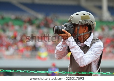 MANDALAY MYANMAR DEC10:Unidentified Photographer in action during the 27th SEA Games Myanmar 2013 match between Myanmar and Philippines at Mandalarthiri Stadium on Dec10 2013 in,MYANMAR.