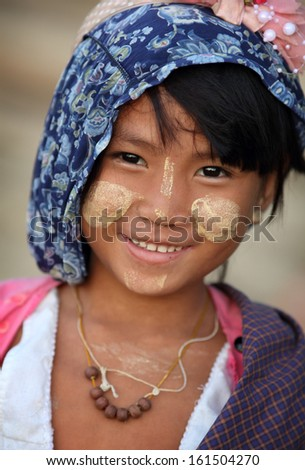 MANDALAY - MYANMAR - DECEMBER 8, 2012: An unidentified smiling Burmese girl on December 8, 2012 in Mandalay, Myanmar. In 2012 an ongoing conflict started between Buddhists and Muslims in Myanmar. - stock photo