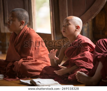 MANDALAY, MYANMAR - DECEMBER 8, 2014. Unidentified Burmese Buddhist novices in Mandalay, Myanmar. In 2012 an ongoing conflict started between Buddhists and Muslims in Myanmar. - stock photo