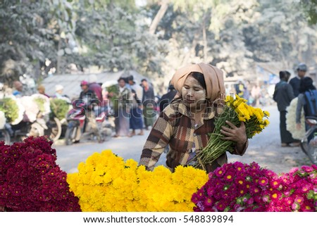 MANDALAY, MYANMAR - FEB 2: Vibrant morning market on the roadside to Mandalay on Feb 2, 2016.  Flowers are principally used in Myanmar as offerings to Buddha, both in homes and temples.