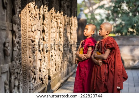 MANDALAY,MYANMAR-FEB 18 : Young monks standing and looking at Shwenandaw Monastery is built in the traditional Burmese architectural style on February 18,2015 in Mandalay,Myanmar. - stock photo