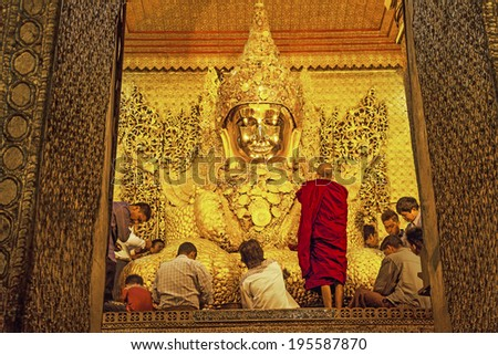MANDALAY, MYANMAR - FEBRUARY 26, 2014: Burmese believers worship Buddha statue pasting gold leaf petals in Mahamuni Pagoda, Mandalay, Myanmar on February 26, 2014. Canon 5D MkII. - stock photo