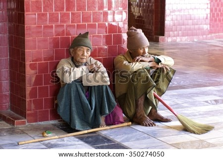 MANDALAY, MYANMAR - FEBRUARY 10, 2007: Inside Mandalay Palace, two old men with brooms leaning against tile wall
