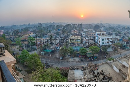 MANDALAY, MYANMAR - FEBRUARY 26, 2013: People on the road and city skyline at dawn.