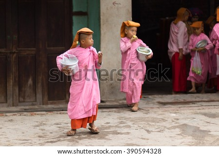 MANDALAY,MYANMAR,JANUARY 17, 2015: A group of young Buddhist nuns is eating rice in the streets of Mandalay, Myanmar (Burma). - stock photo