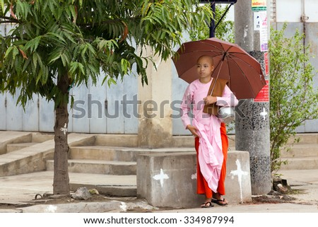 MANDALAY,MYANMAR,JANUARY 17, 2015 : A young Buddhist nuns is standing with her umbrella in the streets of Mandalay, Myanmar (Burma). - stock photo