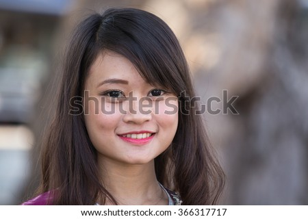 MANDALAY, MYANMAR - JANUARY 16, 2016: Happy Burmese girl poses for a portrait in Mandalay, Burma. The local people are hospitable and friendly to tourists