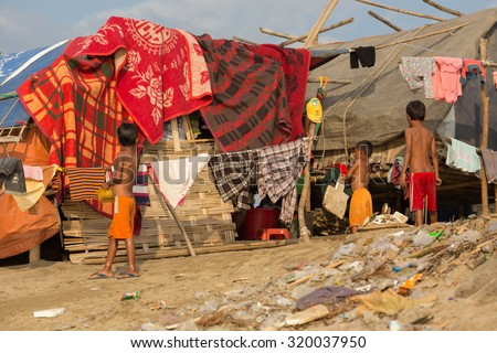 MANDALAY,MYANMAR,JANUARY 17, 2015 : Some kids are standing near a slum house in a very poor and dirty area near the river in Mandalay, Myanmar (Burma). - stock photo