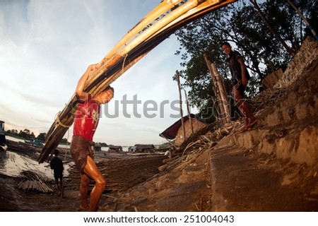 MANDALAY,MYANMAR-JULY 2 : Daily life of Worker carrying bamboo on Port activities in Ayeyarwaddy river for sell on July 2,2014 in Mandalay city, Central of Myanmar.