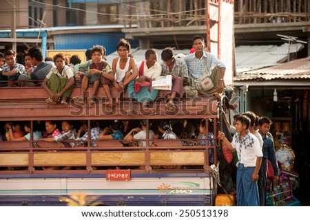 MANDALAY,MYANMAR - JULY 2 : unidentified Burmese peoples in a truck on July 2, 2014 in Mandalay city, Middle of Myanmar. Truck is a popular transportation in Myanmar because it can carry many people.  - stock photo