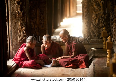 MANDALAY,MYANMAR-JUNE 28 : Three unidentified young Novice Monks studying Pali Buddhist book at Shwenandaw Monastery or Golden Palace Monastery on June 28,2014 in Mandalay city, Middle of Myanmar. - stock photo